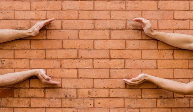 Vorm gemaakt door menselijke handen op bakstenen muur