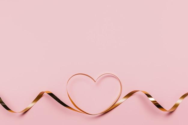 Vorm hart door gouden lint op geïsoleerde roze achtergrond