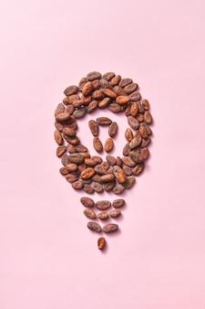 Vorm van gloeilamp gemaakt van natuurlijke biologische droge cacaobonen op een lichtroze achtergrond met kopieerruimte. effect van verbeterde menselijke hersenactiviteit van chocolade.