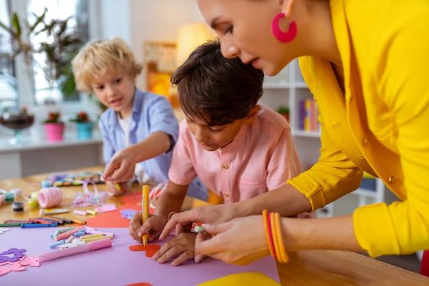 Vorm van hart. jonge leraar die roze oorbellen draagt en jongen helpt om uitsnede in de vorm van een hart te maken