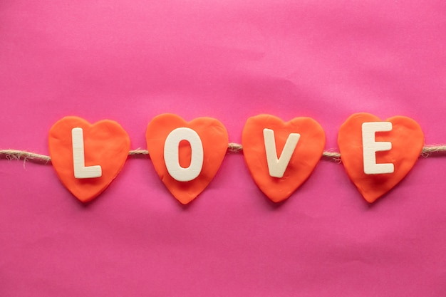 Vorm van hart, woord liefde in rode harten op roze achtergrond, liefde pictogram, valentijnsdag