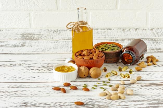 Vormen van omega- of visoliesupplementen - gelcapsules. vloeibare olie en noten op houten tafel. gezond dieet.