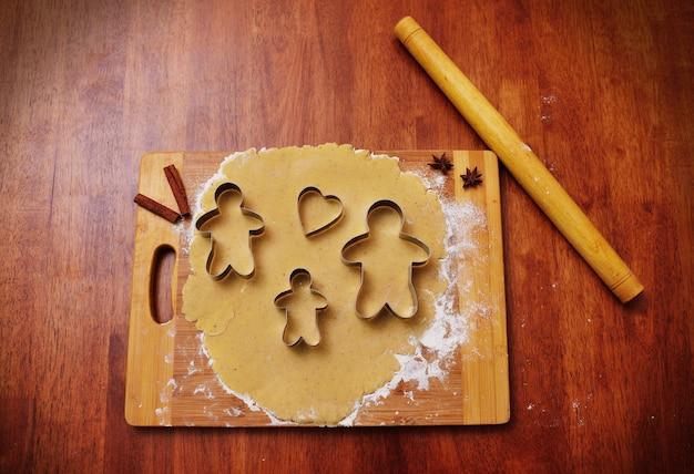 Vormen voor het bakken van peperkoek in de vorm van een man en een hart op de achtergrond van een deegroller