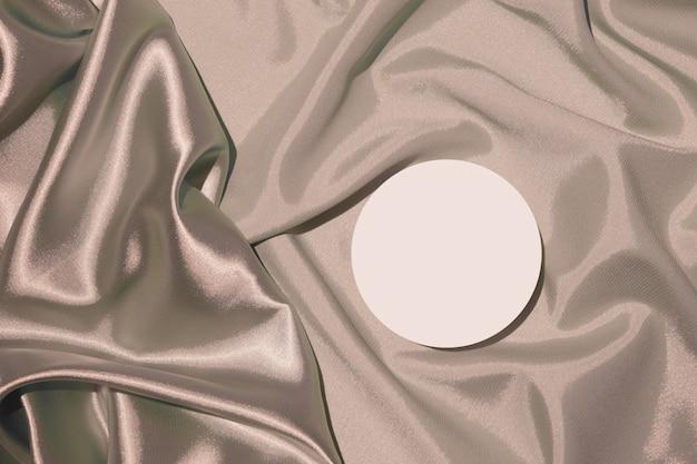Vouwen van beige satijnen stof en podiumvoetstuk voor cosmetica of parfum bovenaanzicht