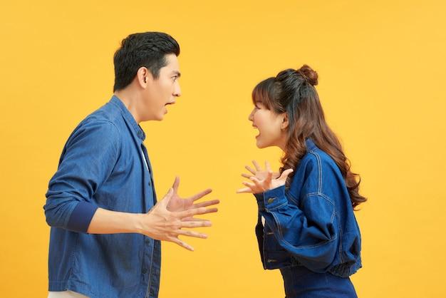 Vprofile zijaanzicht portret van twee aantrekkelijke boze agressieve nerveuze mensen met strijd woede schuld geïsoleerd over levendige glans fel oranje achtergrond. negatief emotiesconcept.