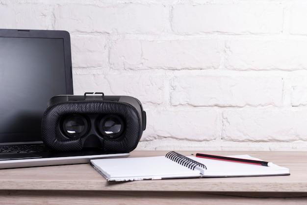 Vr-apparaat met laptop op een houten tafel in de buurt van een bakstenen witte muur