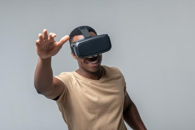 Vr-bril. glimlachende afro-amerikaanse man virtuele bril in lichte tshirt zwaaien met zijn handen op grijze achtergrond