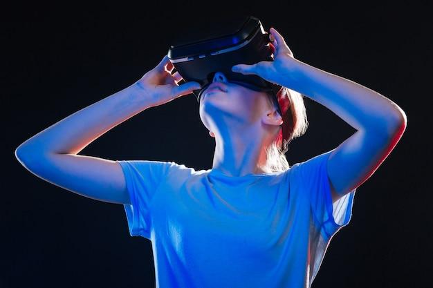 Vr-concept. slimme jonge vrouw met behulp van vr-bril tijdens het testen van nieuwe technologie