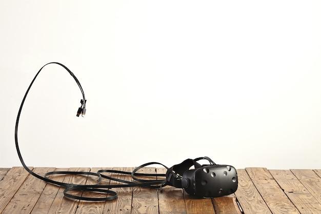 Vr-headset en enkele koorden op ruwe rustieke houten tafel op witte muur