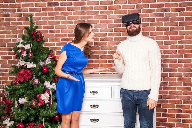 Vr-technologie en conflict tussen paar. man met vr-headset en zijn vrouw is boos op nieuwjaar.