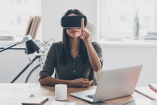 Vr-technologieën. zelfverzekerde jonge vrouw in virtual reality-headset die in de lucht wijst terwijl ze op haar werkplek op kantoor zit