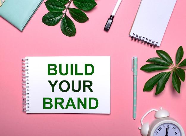 Vraag build your brand staat in het groen op een wit notitieblok op een roze achtergrond
