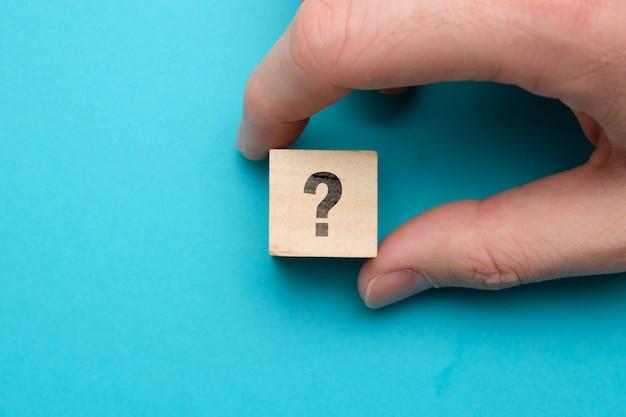 Vraag en taakconceptenhand met pictogrammen op houten blokken.