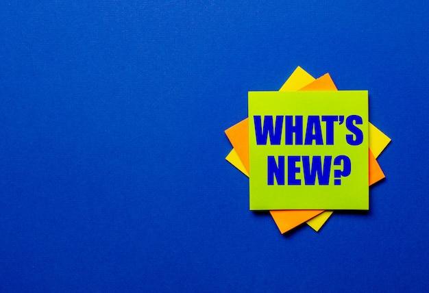 Vraag wat is nieuw is geschreven op heldere stickers op een blauwe tafel