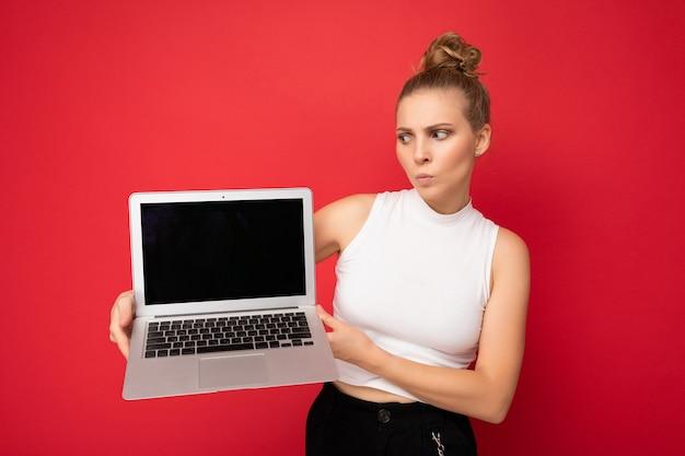 Vraagt blonde jonge vrouw met verzamelde haren met twijfels kijken naar netbook toetsenbord