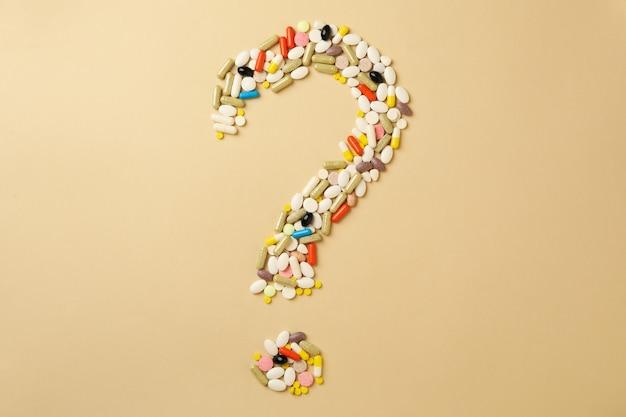 Vraagteken gemaakt van pillen op beige