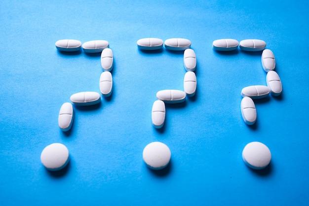 Vraagteken gemaakt van witte pillen op een blauw