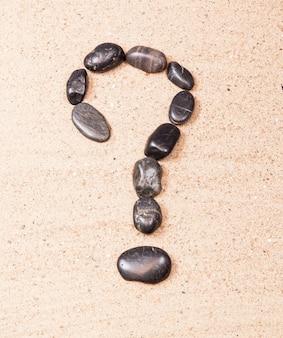 Vraagteken getekend met kiezels op het zand van een strand