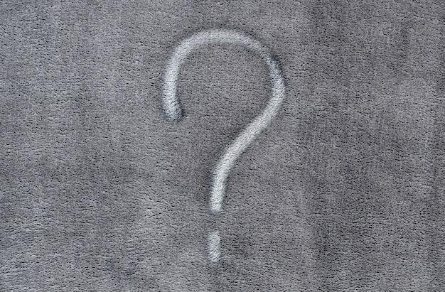 Vraagteken op de grijze achtergrond van de stoffentextuur