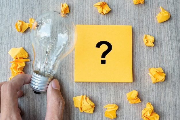 Vraagteken (?) woord op gele notitie en verkruimeld papier