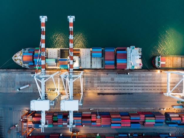Vrachtcontainerschip bij de haven van de lading internationale werf en de tank van de kraanlading voor de uitvoer