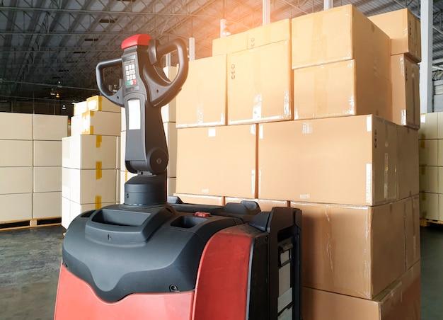 Vrachtdozen verzending verpakking fabriek en opslag stapel kartonnen dozen op pallet en vorkheftruck palletkrik bij de opslag van het magazijn
