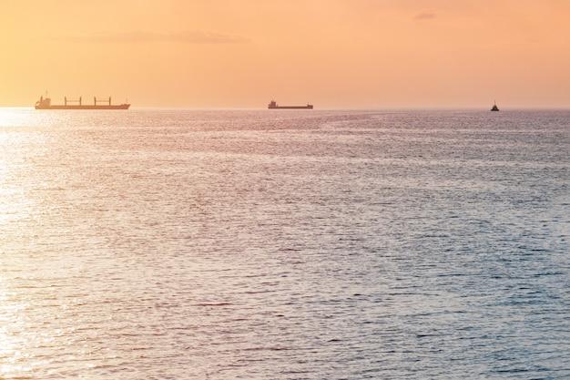 Vrachtschepen en binnenschip bij mooie zonsondergang