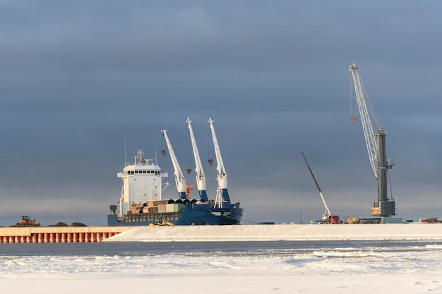 Vrachtschip afgemeerd in arctische haven wintertijd ijsnavigatie bezig met laden