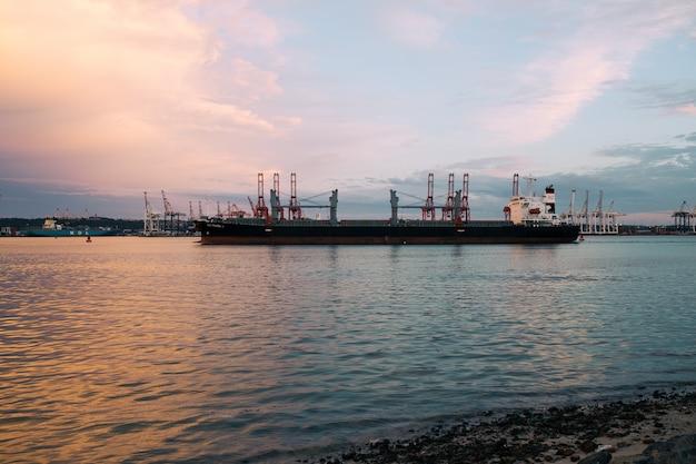 Vrachtschip dat bij de haven op een zonnige dag tijdens zonsondergang wordt geparkeerd