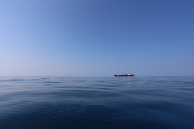 Vrachtschip op de zee in een heldere dag en heldere hemel.