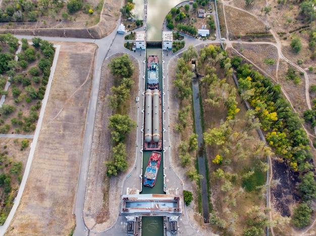 Vrachtvervoer over water van petrochemische apparatuur in rusland. de goederentrein van sleepboten passeert de eerste sluis van het wolga-don-navigatiekanaal in volgograd. rusland