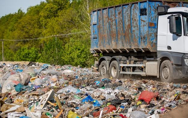 Vrachtwagen die huisvuil en afval van het huishouden naar de stortplaats, ecologieconcept brengt