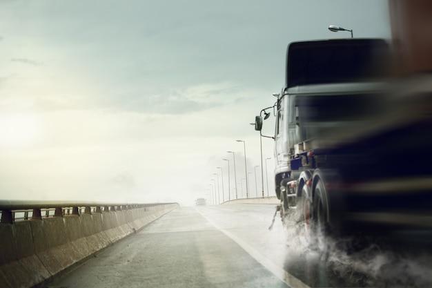 Vrachtwagen die zich snel op natte weg na zware regen, slecht weer cond beweegt