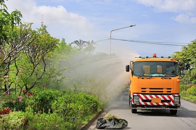 Vrachtwagen drenken een boom door spuitwater in het park in de ochtend.