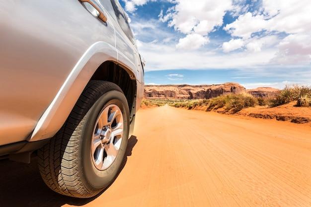Vrachtwagen in woestijn met bergen op de achtergrond.