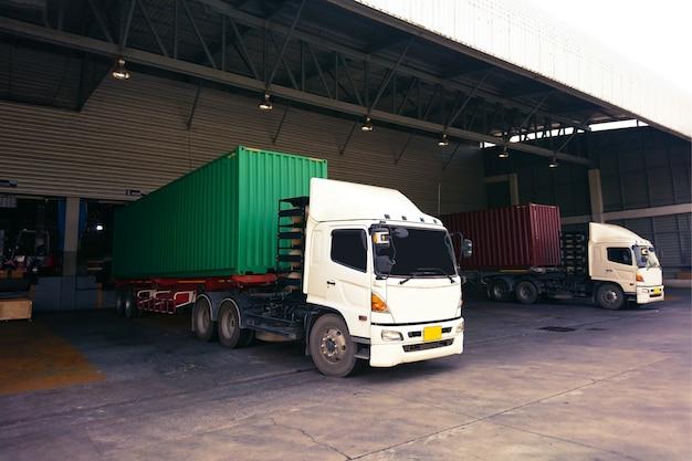 Vrachtwagen industrieel met groene en rode containerwerf met vorkheftruck die in groot ladingspakhuis werken voor logistiek.
