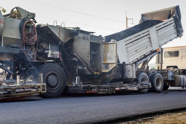 Vrachtwagen is het lossen van asfalt naar machine voor reparatie weg