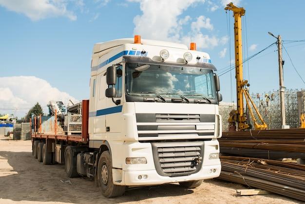 Vrachtwagen met een laadkraan op een bouwplaats, vooraanzicht