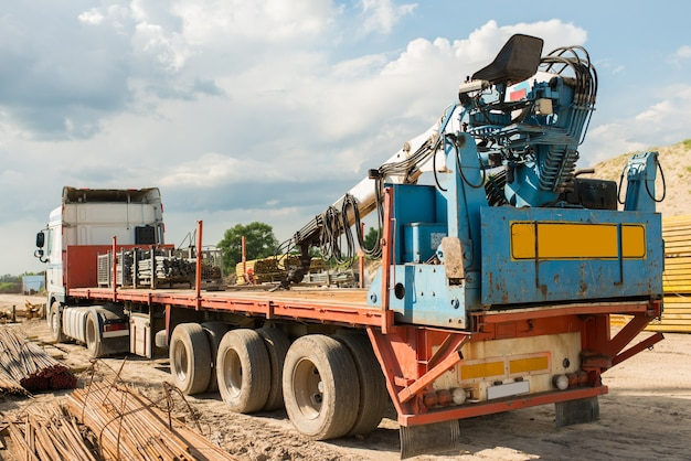 Vrachtwagen met laadkraan op bouwplaats, achteraanzicht