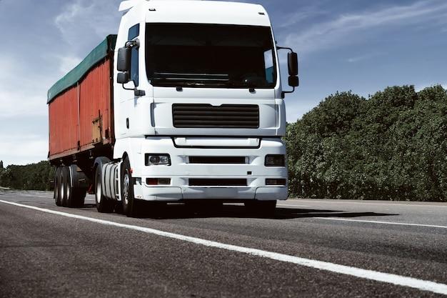 Vrachtwagen op de weg, vooraanzicht, lege ruimte op een rode container -
