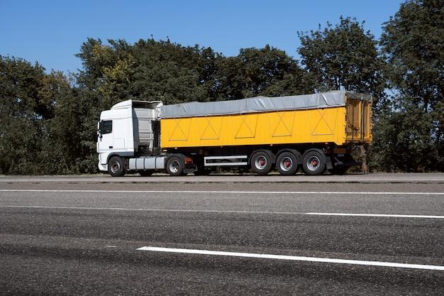Vrachtwagen op de weg, zijaanzicht, lege ruimte op een gele container