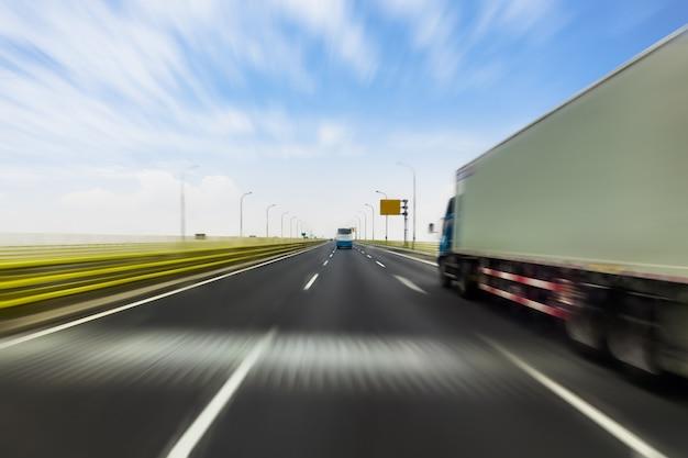 Vrachtwagen op een snelle uitdrukkelijke weg, bewegingsonduidelijk beeld