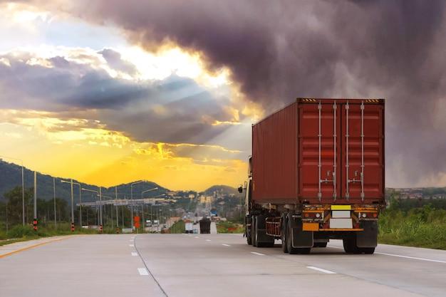 Vrachtwagen op snelwegweg met rode container, transportconcept., import, export logistiek industrieel transport over land op de snelweg met zonsopganghemel en erg bewolkt