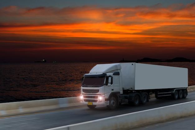Vrachtwagen op wegweg met container, logistisch industrieel vervoer met zonsopganghemel