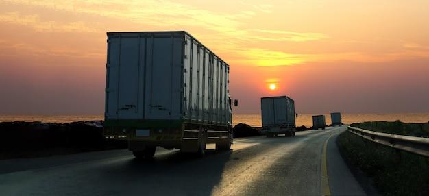 Vrachtwagen op wegweg met container, logistische industrieel met zonsopganghemel