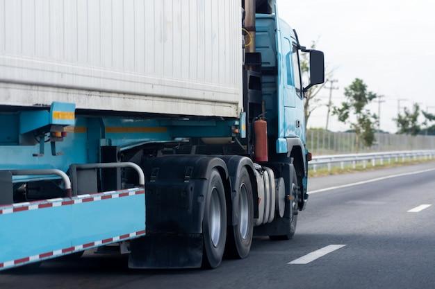 Vrachtwagen op wegweg met container, vervoer op de asfaltuitgang