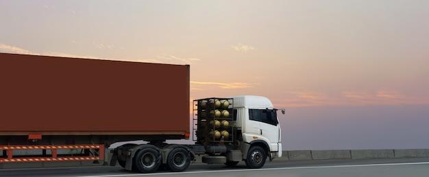 Vrachtwagen op wegweg met rode container, logistische industrieel met zonsopganghemel