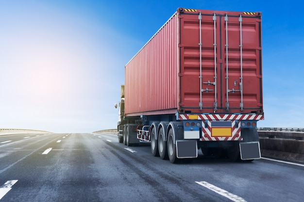 Vrachtwagen op wegweg met rode container. vervoer op de asfalt snelweg