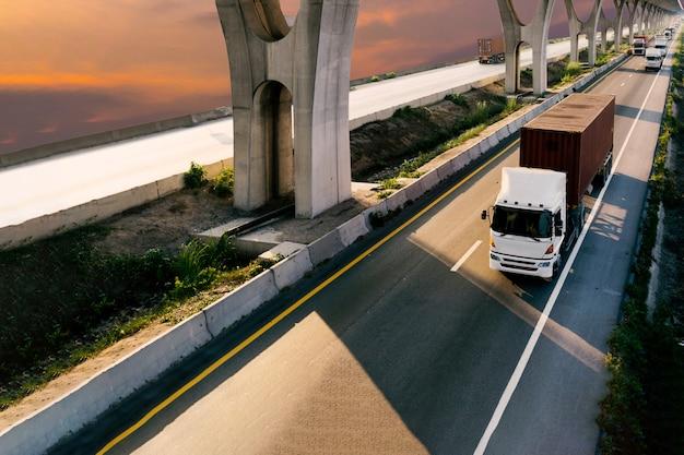 Vrachtwagen op wegweg met rode container, vervoer op de asfaltsnelweg met zonsopganghemel