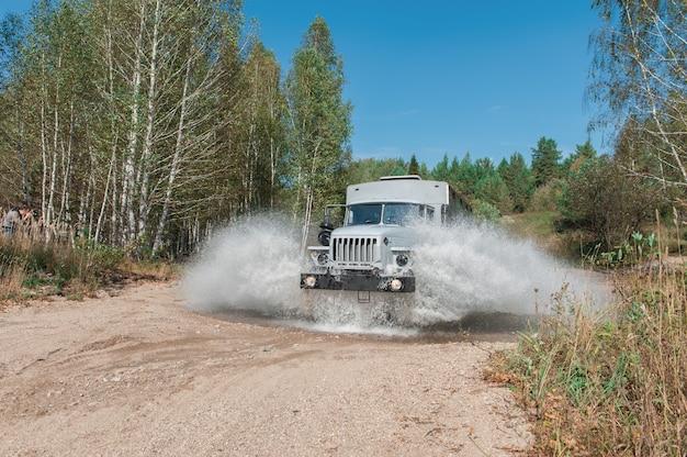 Vrachtwagen passeert een plas